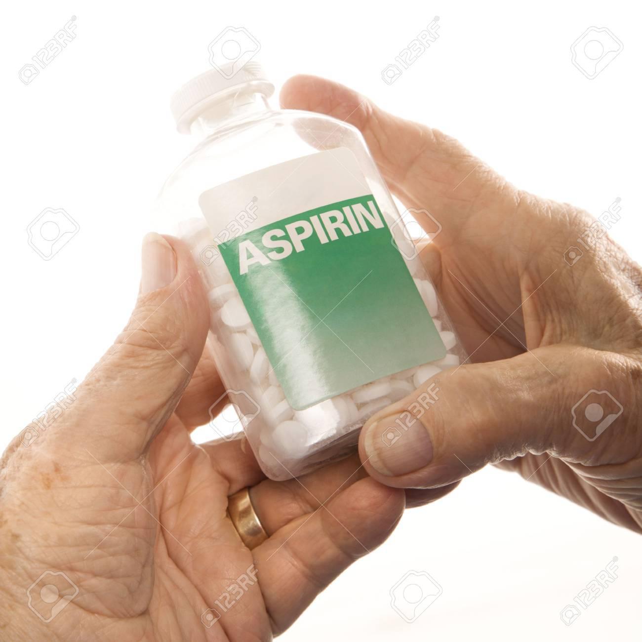 Close-up of elderly male Caucasion hands holding aspirin bottle. - 2246016