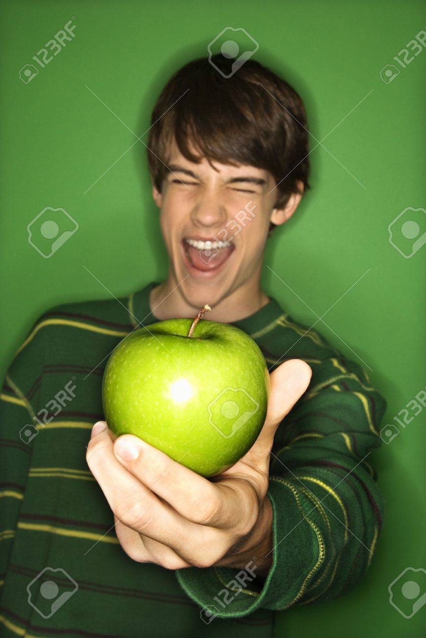Portrait of Caucasian teen boy holding apple out in hand and making facial expression. Stock Photo - 2376393