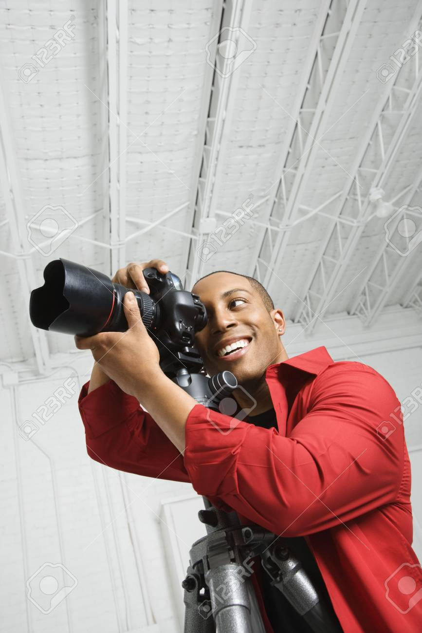 African American young male adult looking through camera on tripod. Stock Photo - 2425953