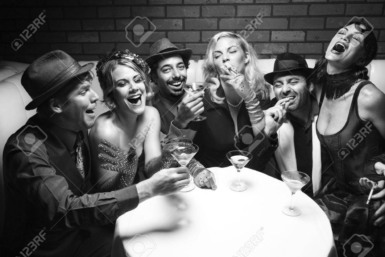 Group of Caucasian prime adult retro males and females sitting at table in lounge laughing. Stock Photo - 2376369