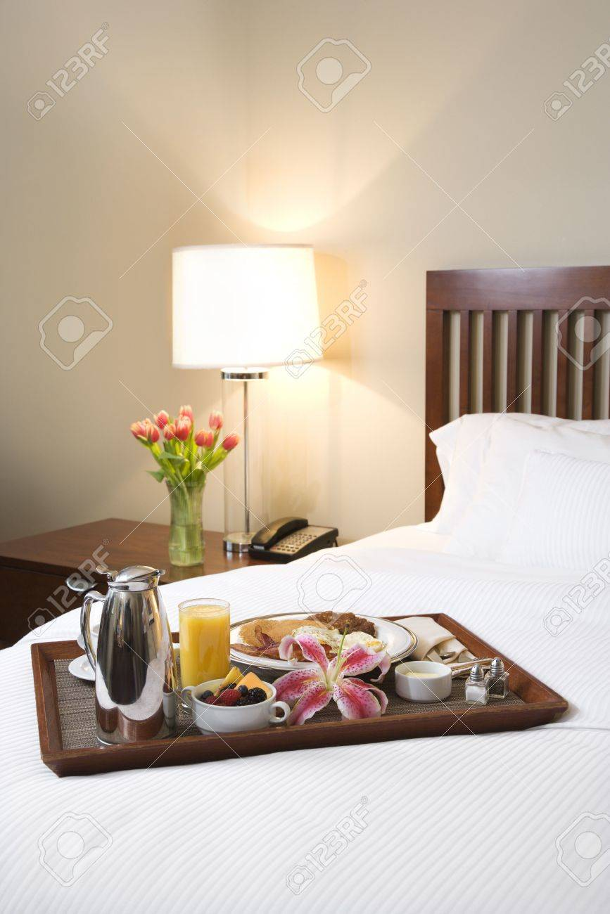Breakfast tray laying on white bed in upscale hotel. Stock Photo - 2537793