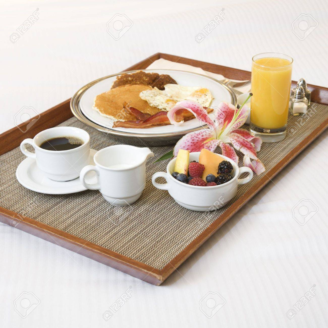close-up of breakfast tray laying on white bed. stock photo