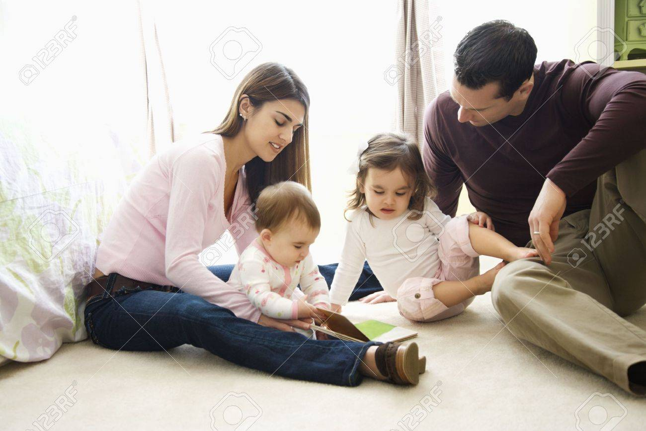 Children with mother and father sitting on bedroom floor looking at book. Stock Photo - 2555692