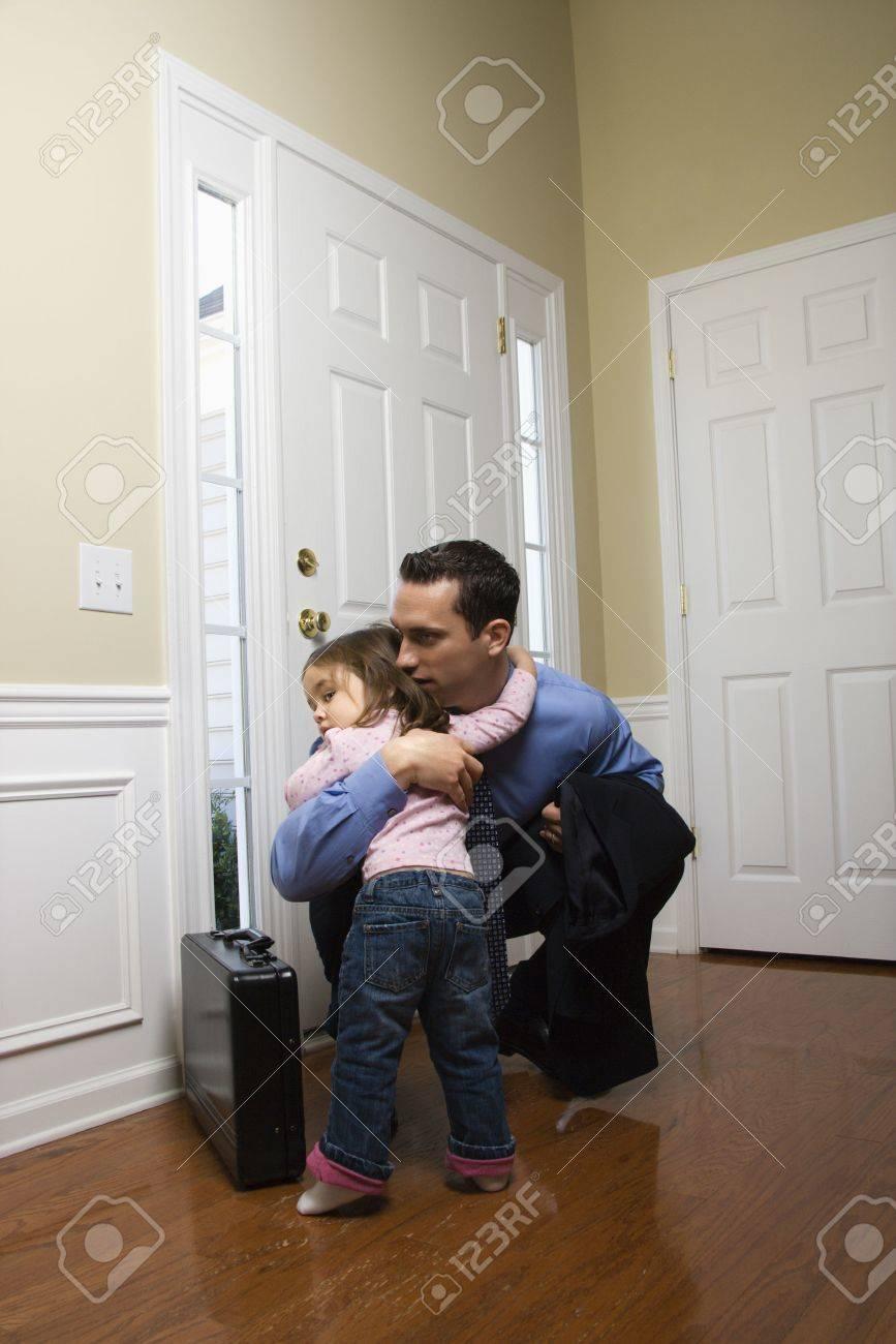 Caucasian businessman   at door with briefcase hugging daughter. Stock Photo - 2555112