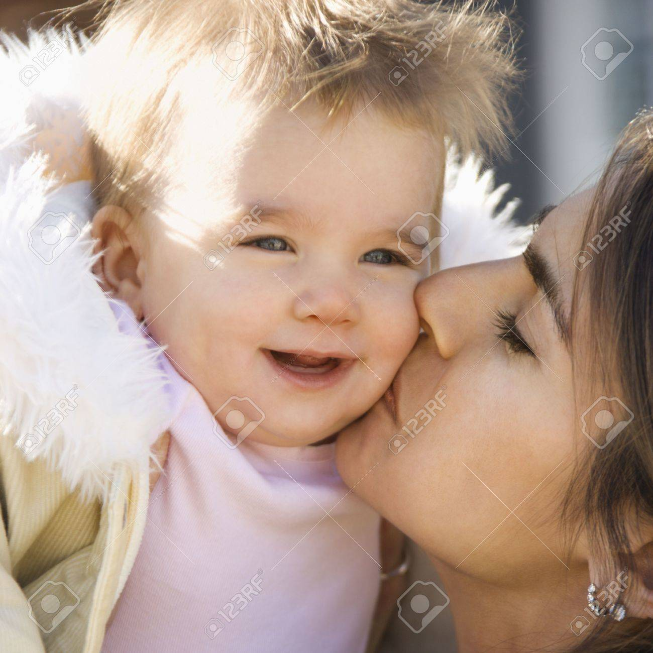 Caucasian mother holding and kissing smiling baby girl. Stock Photo - 2555185