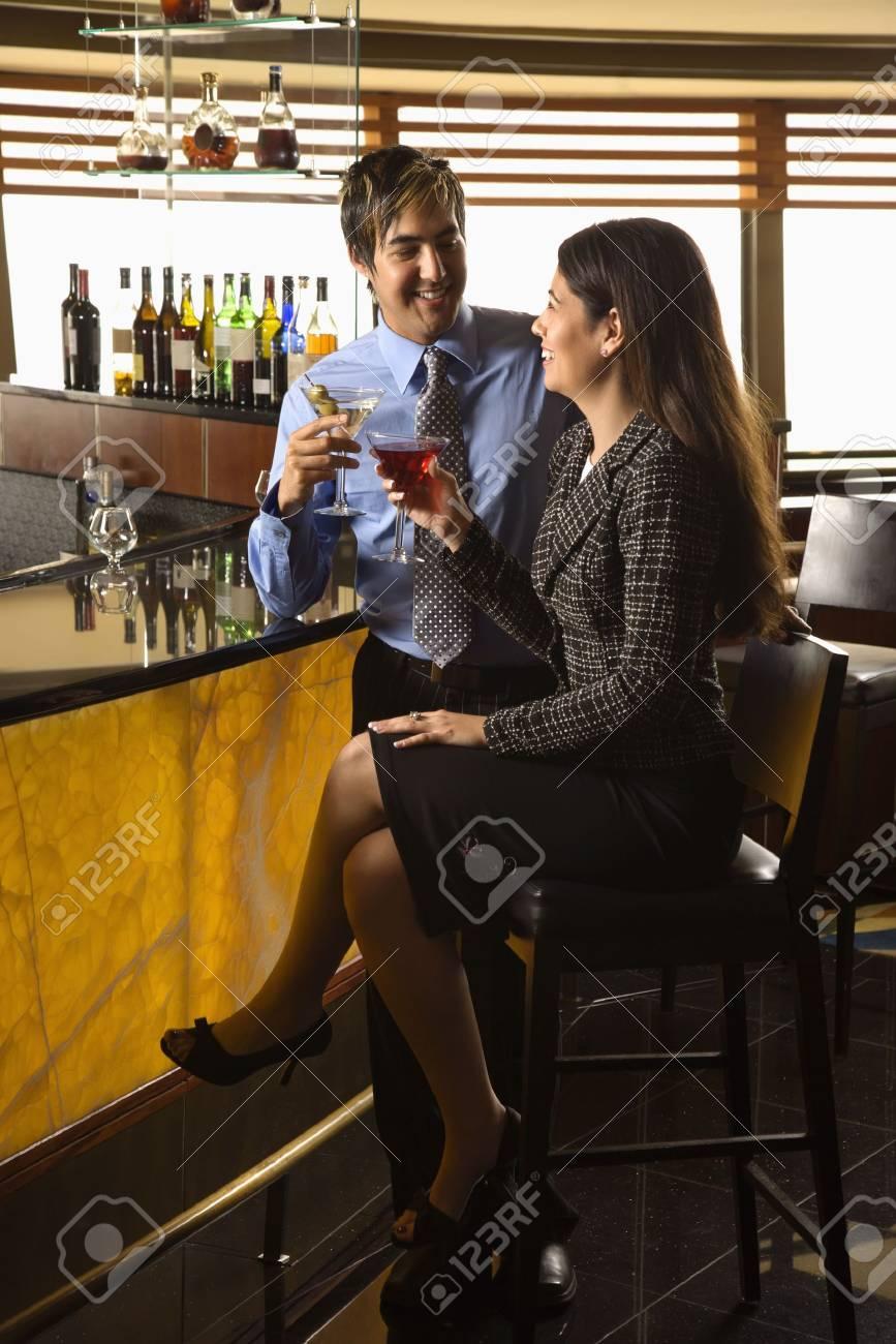 Mid adult Hispanic couple toasting at bar. Stock Photo - 2555192