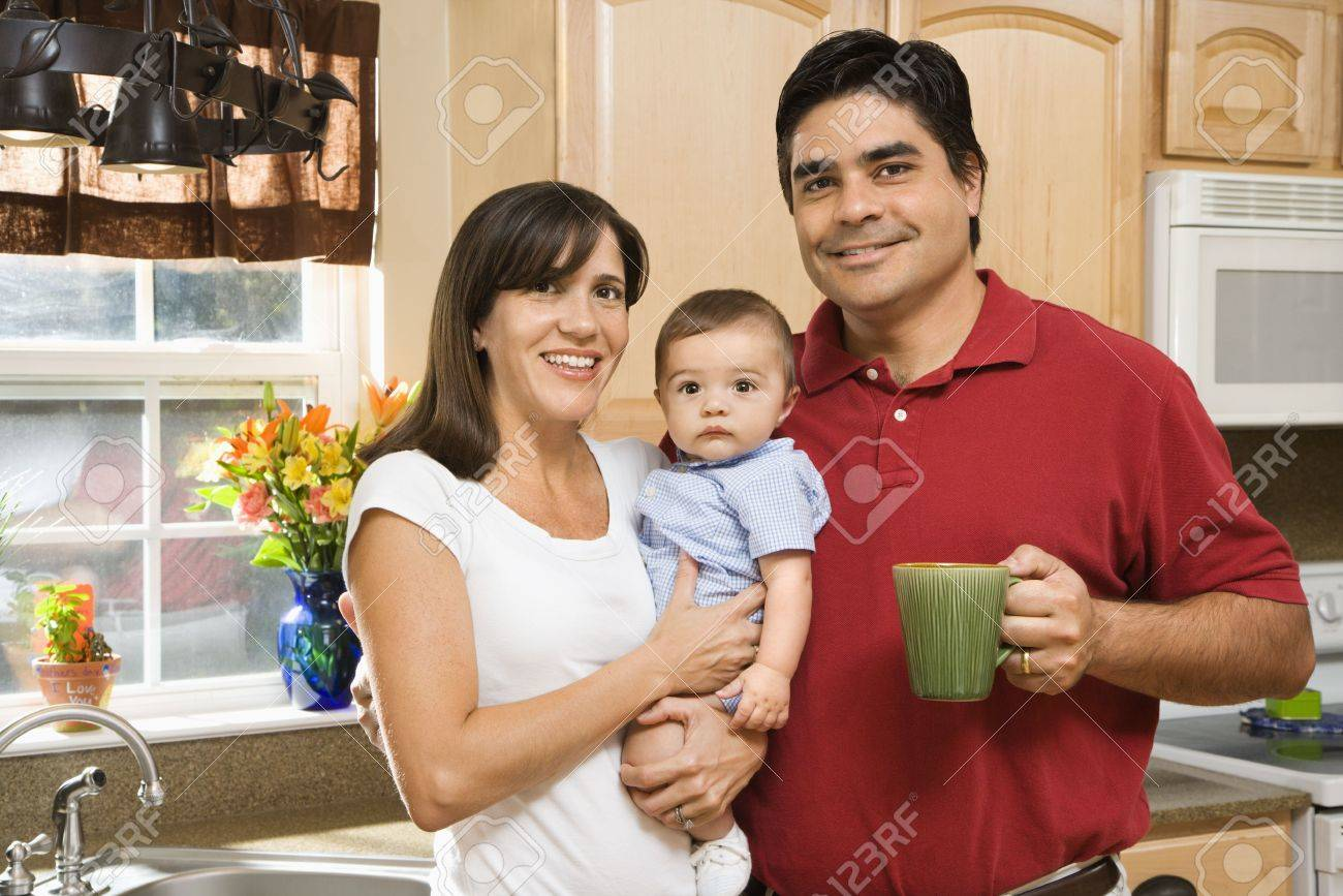 Hispanic family portrait in home kitchen with baby. Stock Photo - 2555946