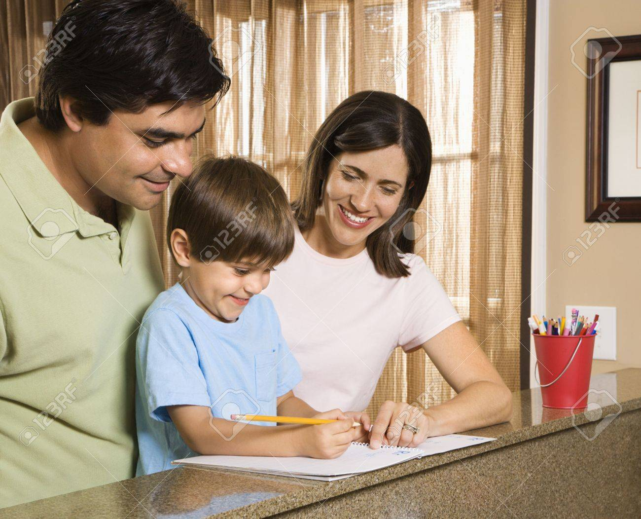 Hispanic parents helping son with homework. Stock Photo - 2555983
