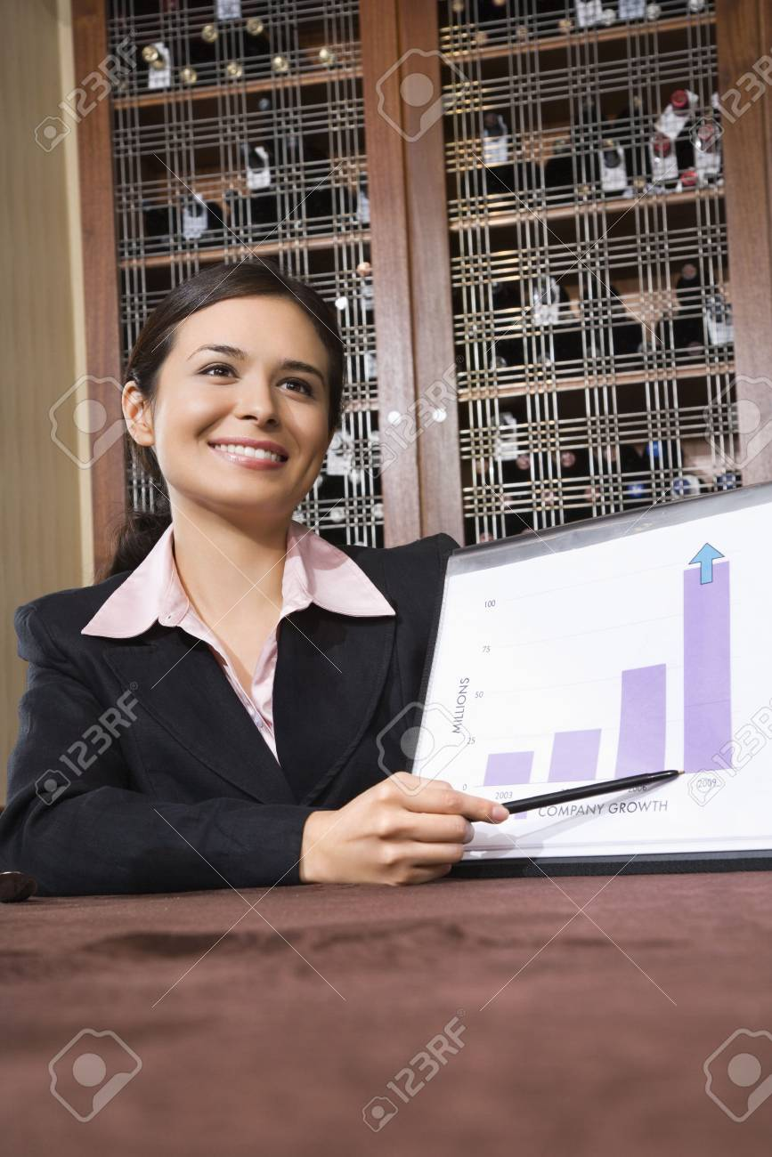 Pretty businesswoman smiling and pointing to bar graph. Stock Photo - 2616054