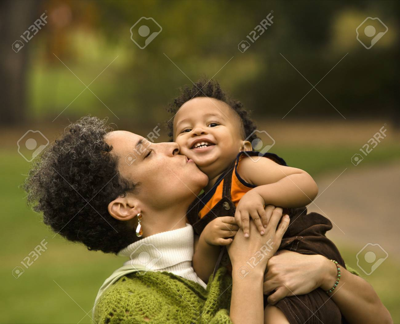 Head and shoulder portrait of woman holding and kissing boy as he smiles. Stock Photo - 2615947