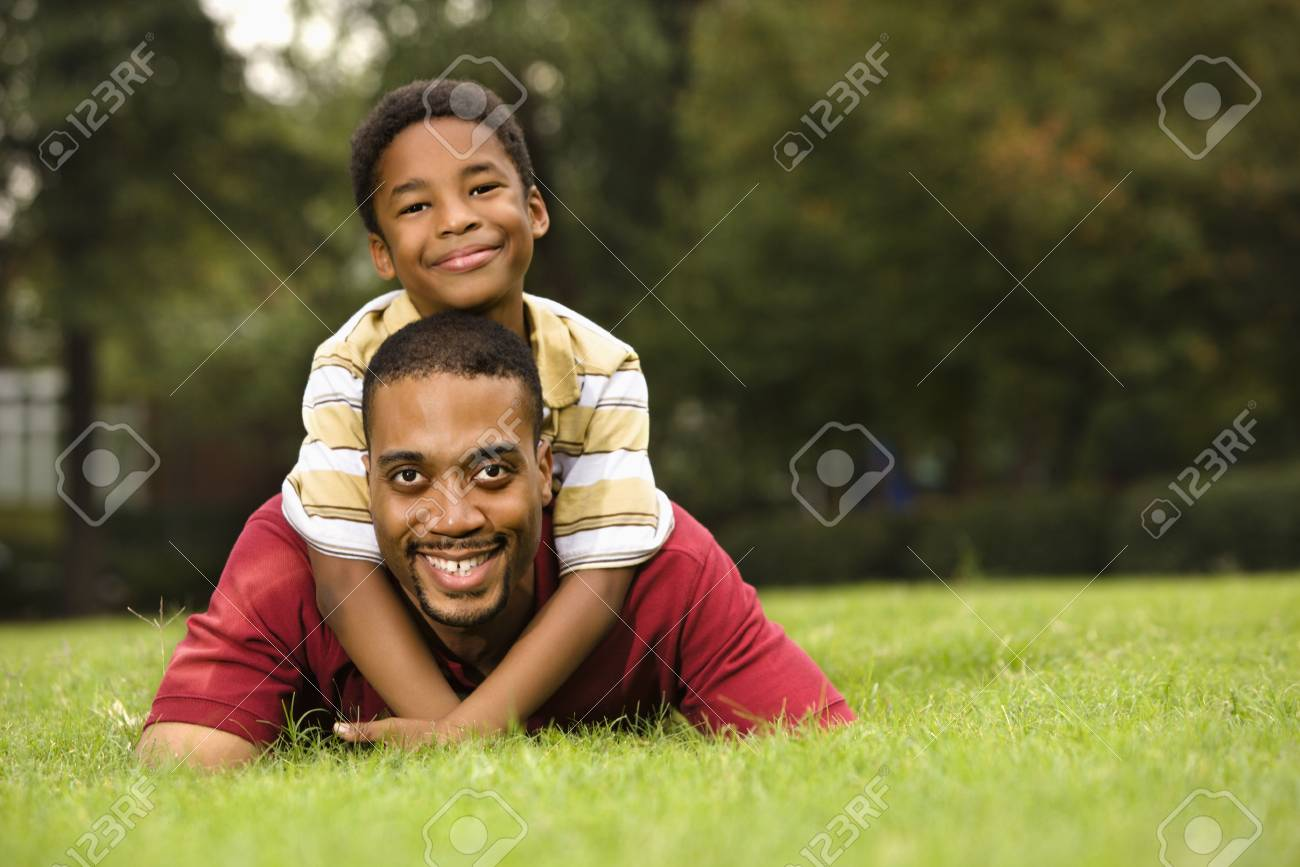 Father lying in grass smiling as son climbs on his back and hugs his neck. Stock Photo - 2615753
