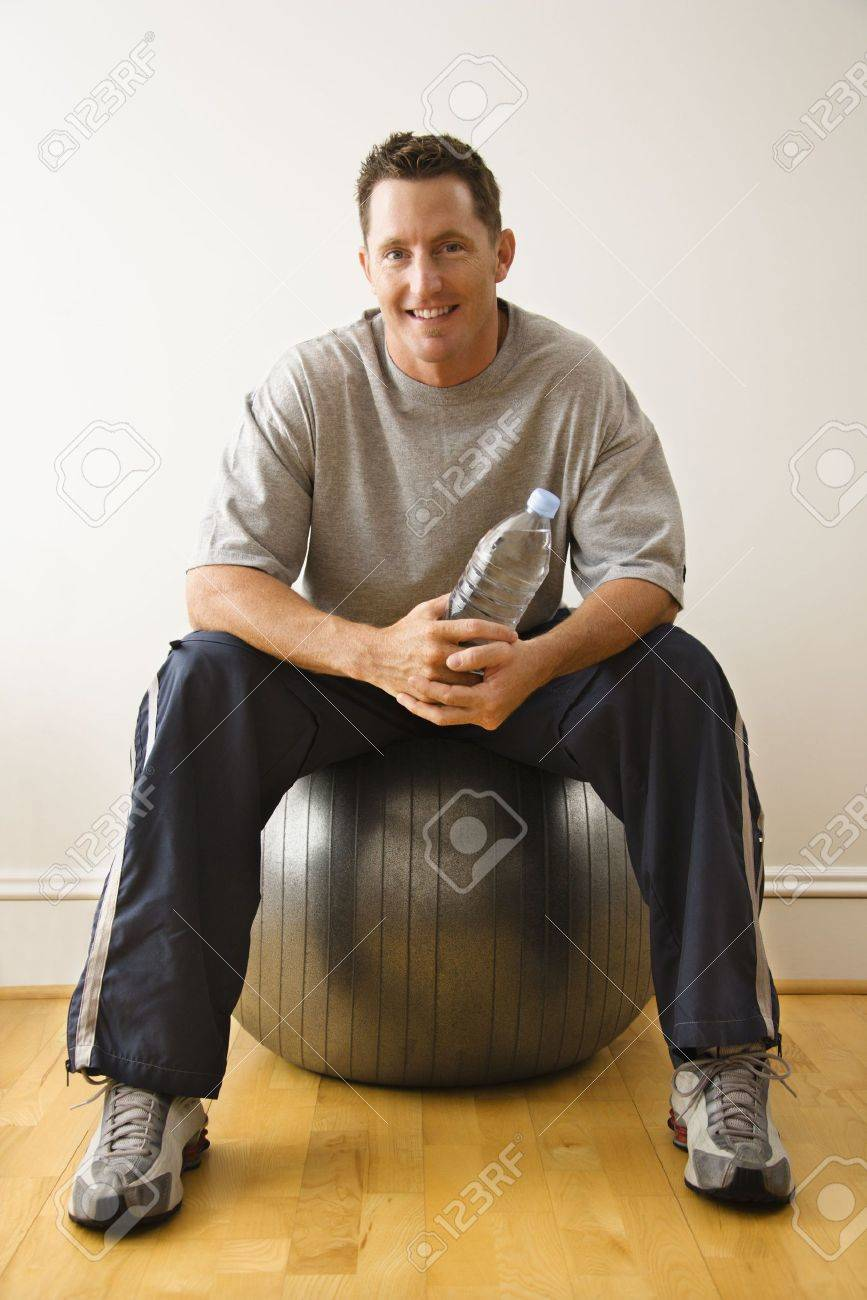 Man holding water bottle sitting on balance ball at gym smiling. Stock Photo - 2615835