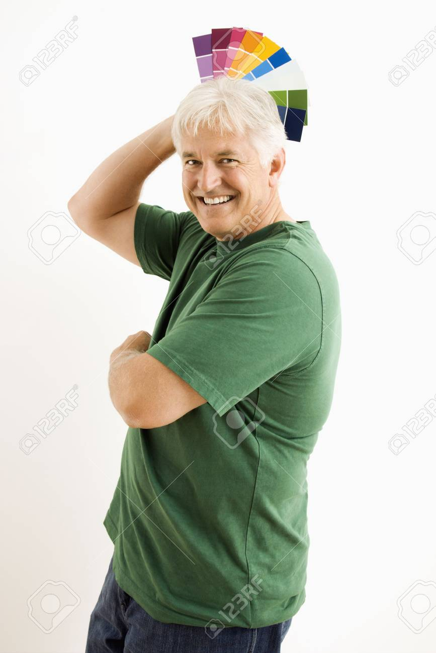 Middle-aged man fanning paint swatches over his head. Stock Photo - 3557437