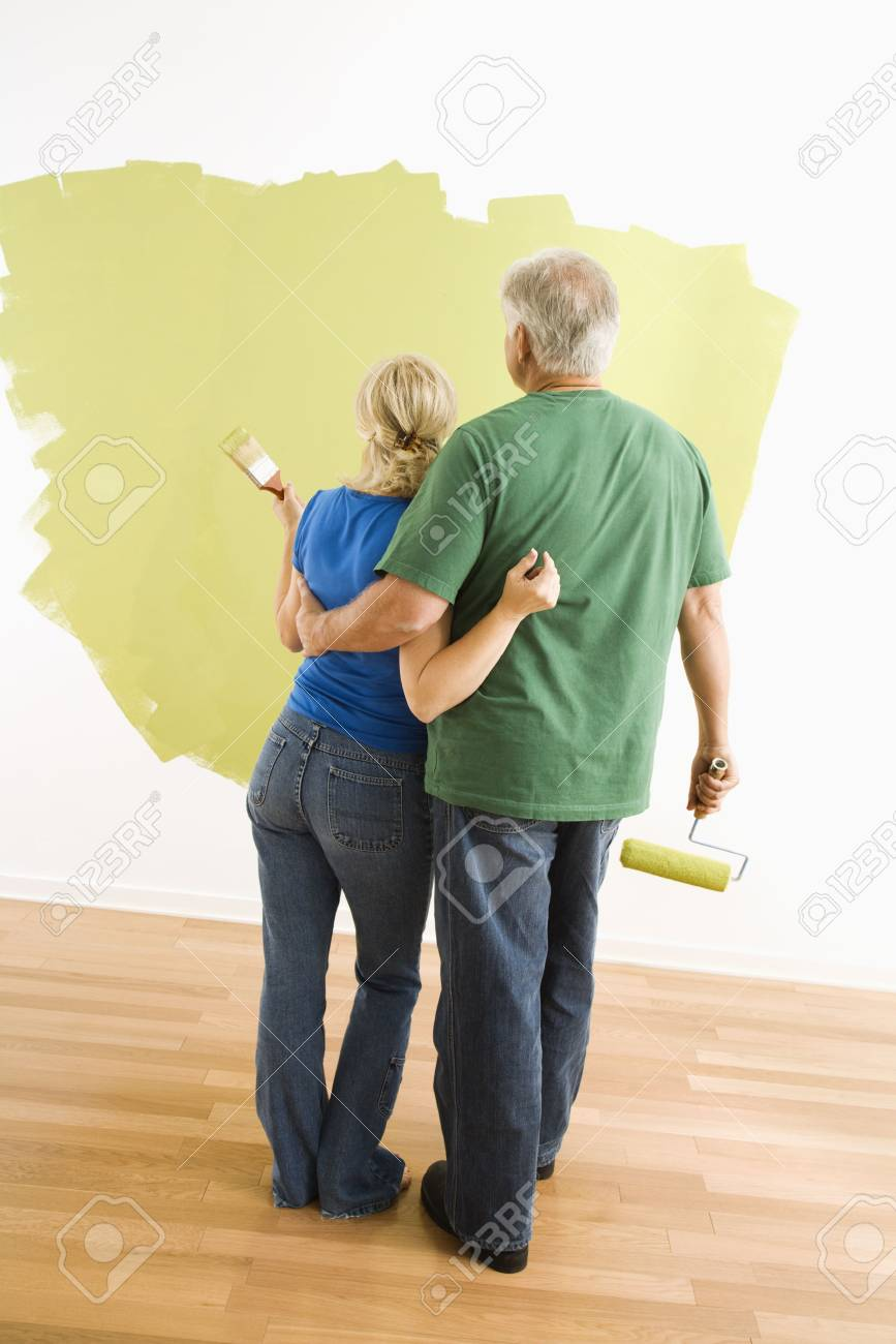 Middle-aged couple painting wall green observing their work. Stock Photo - 3557434