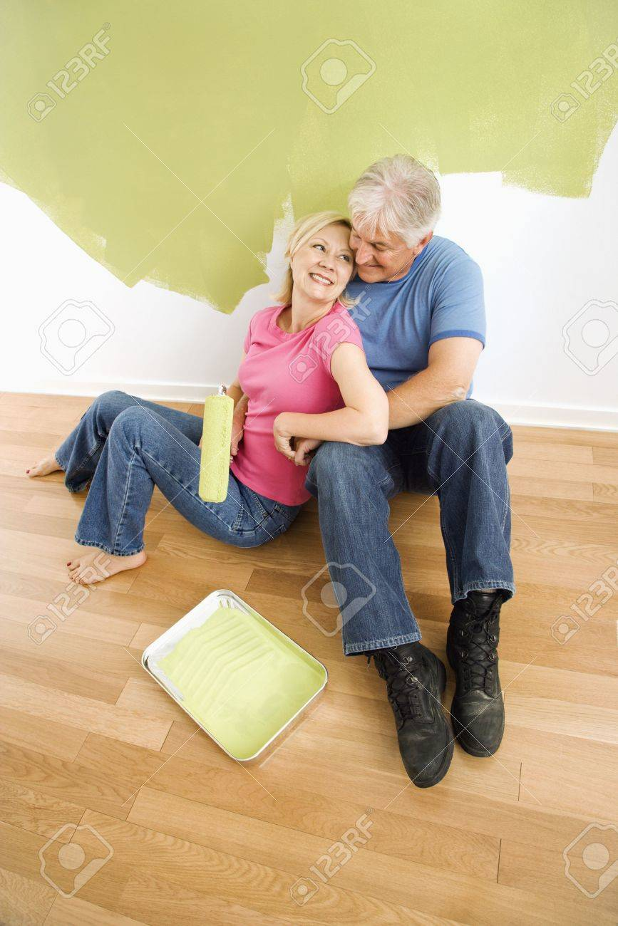 Wall Painting Supplies portrait of happy adult couple sitting in front of half-painted