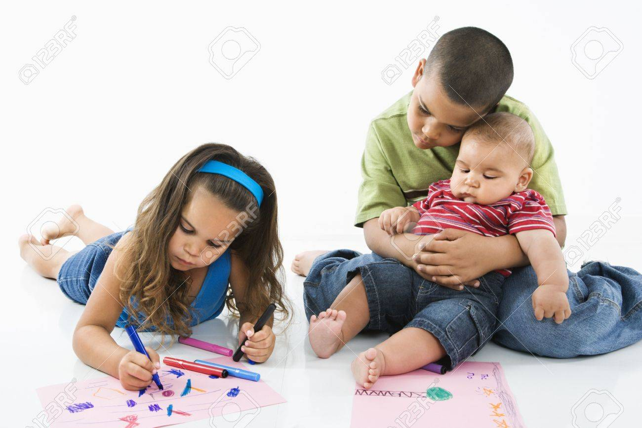 Young latino girl coloring on construction paper while brothers watch. Stock Photo - 3589418