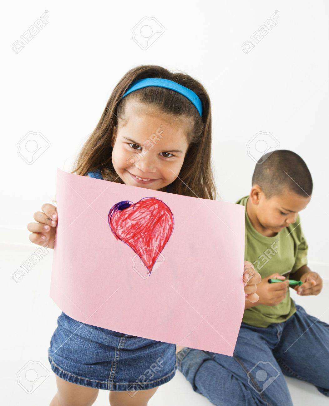 Young girl showing off drawing of heart while boy sits behind her. Stock Photo - 3589262