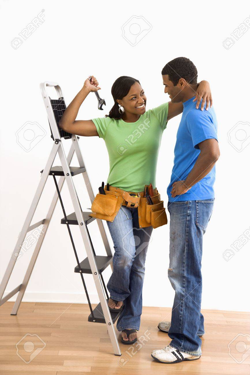 Portrait of smiling African American male and female couple with home repair tools and ladder. Stock Photo - 3589382