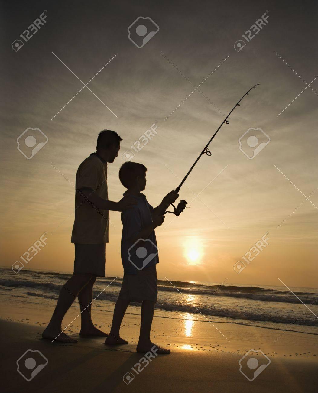 Padre E Hijo De Pesca En El Océano Surf Al Atardecer. Verticalmente ...