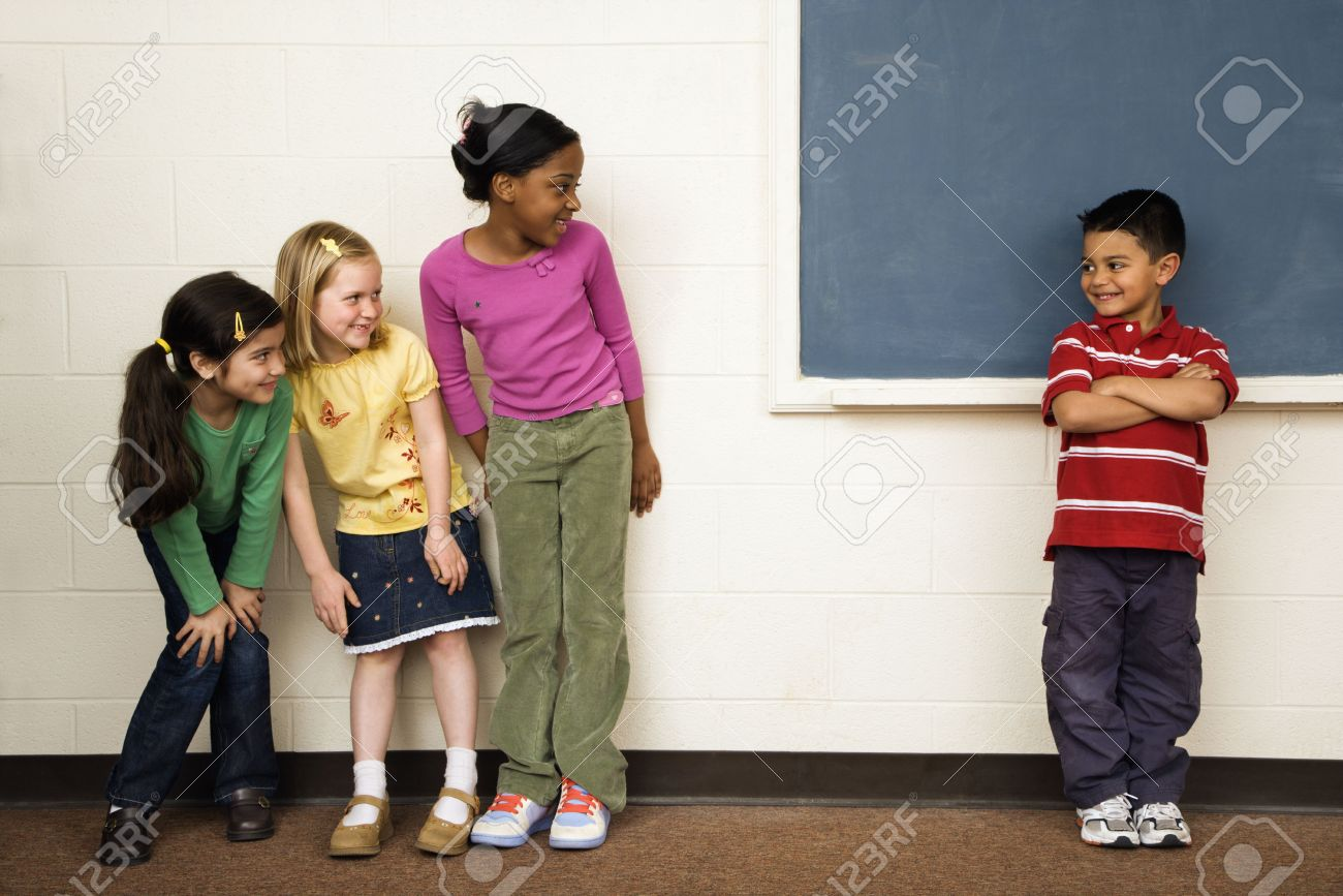 Students standing in classroom. A boy is separate from the girls. Horizontally framed shot. Stock Photo - 6235574