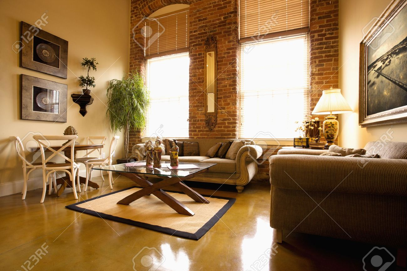 interior of furnished living room with large windows and brick