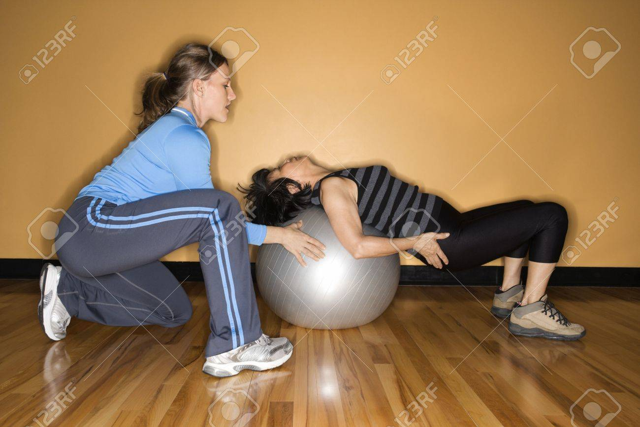 Woman steadies a balance ball for another woman lying back on it at the gym. Horizontal shot. Stock Photo - 6420922