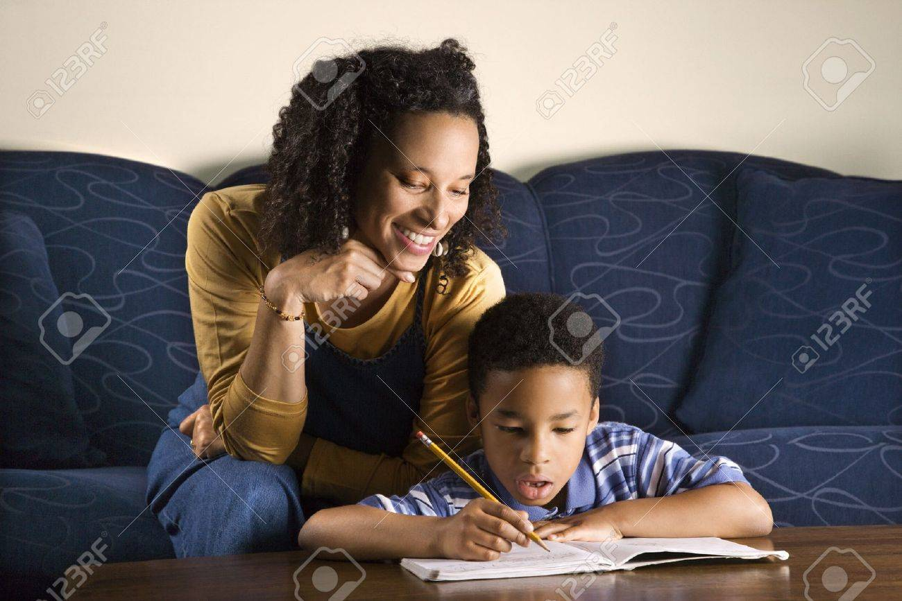 A mid adult African American woman sits on a couch and helps her young some with his homework. Horizontal shot. Stock Photo - 6455398