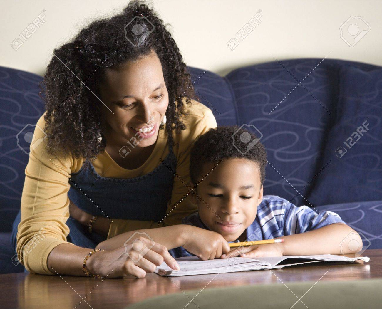 A mid adult African American woman sits on a couch while helping her young some with his homework. Horizontal shot. Stock Photo - 6455370