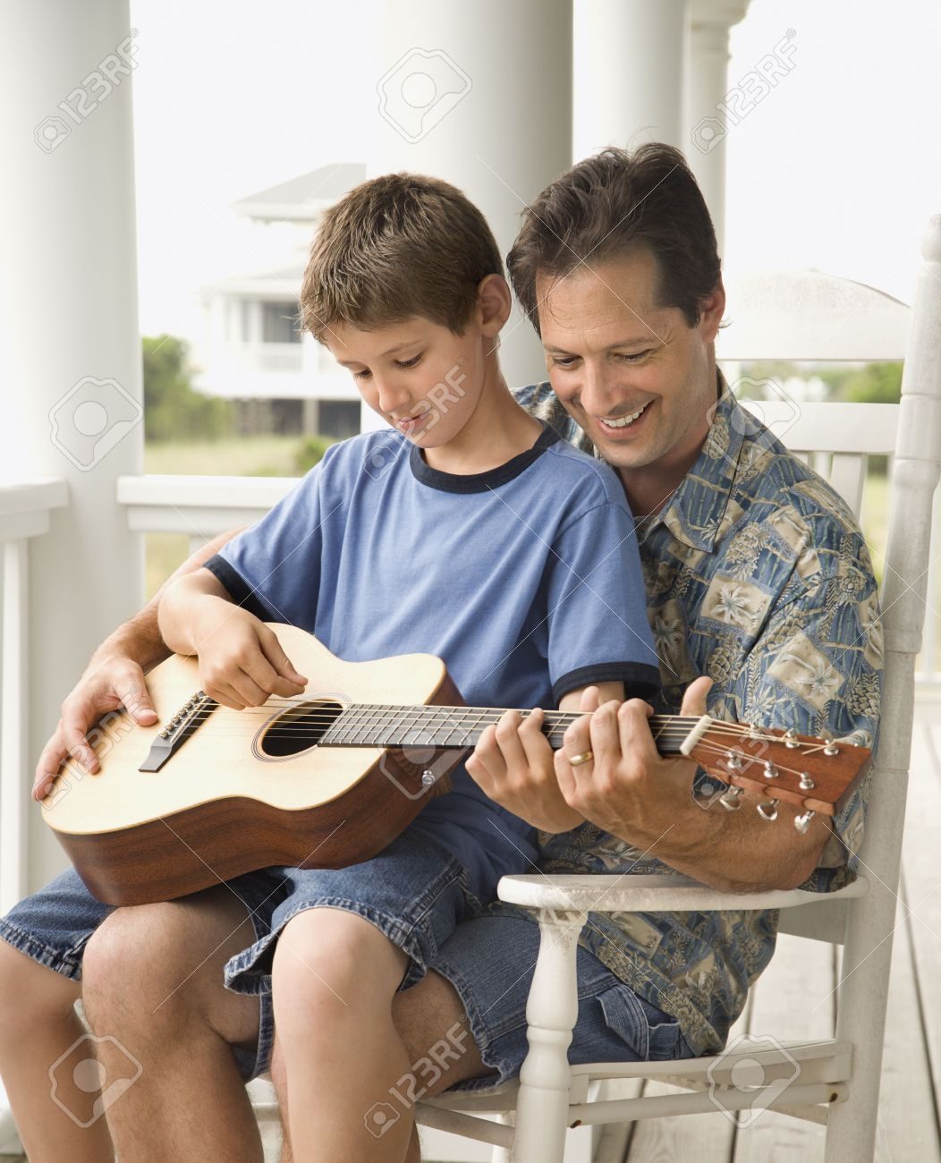 Son sits on his father's lap while playing guitar. Vertical shot. Stock Photo - 6455266