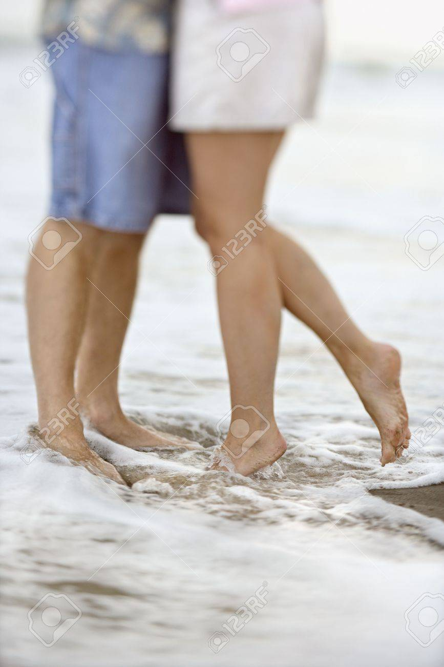 Waist down image of affectionate couple standing in the water at the beach. Vertical shot. Stock Photo - 6395731