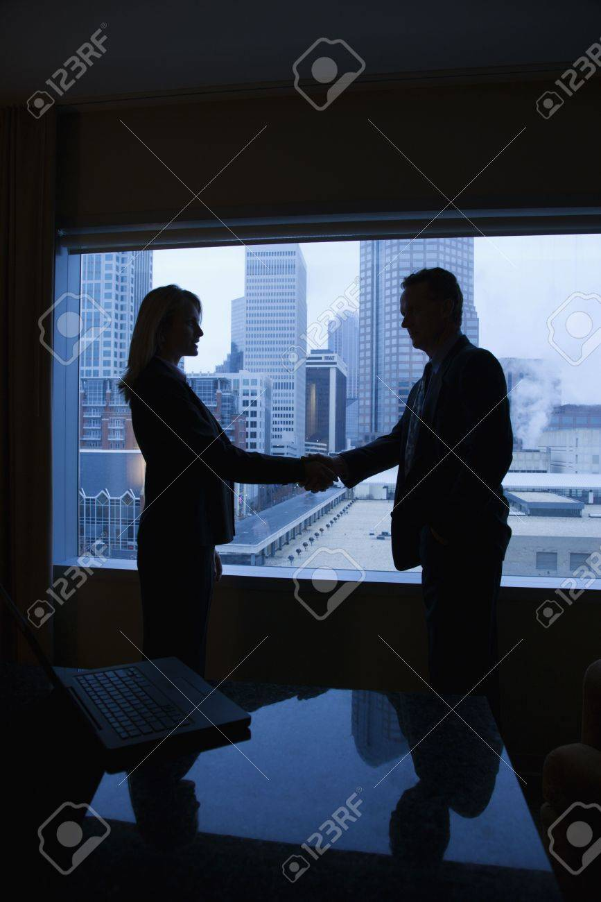 Silhouette of a businessman and businesswoman shaking hands. The city can be seen through the window in the background. Vertical shot. Stock Photo - 6420902