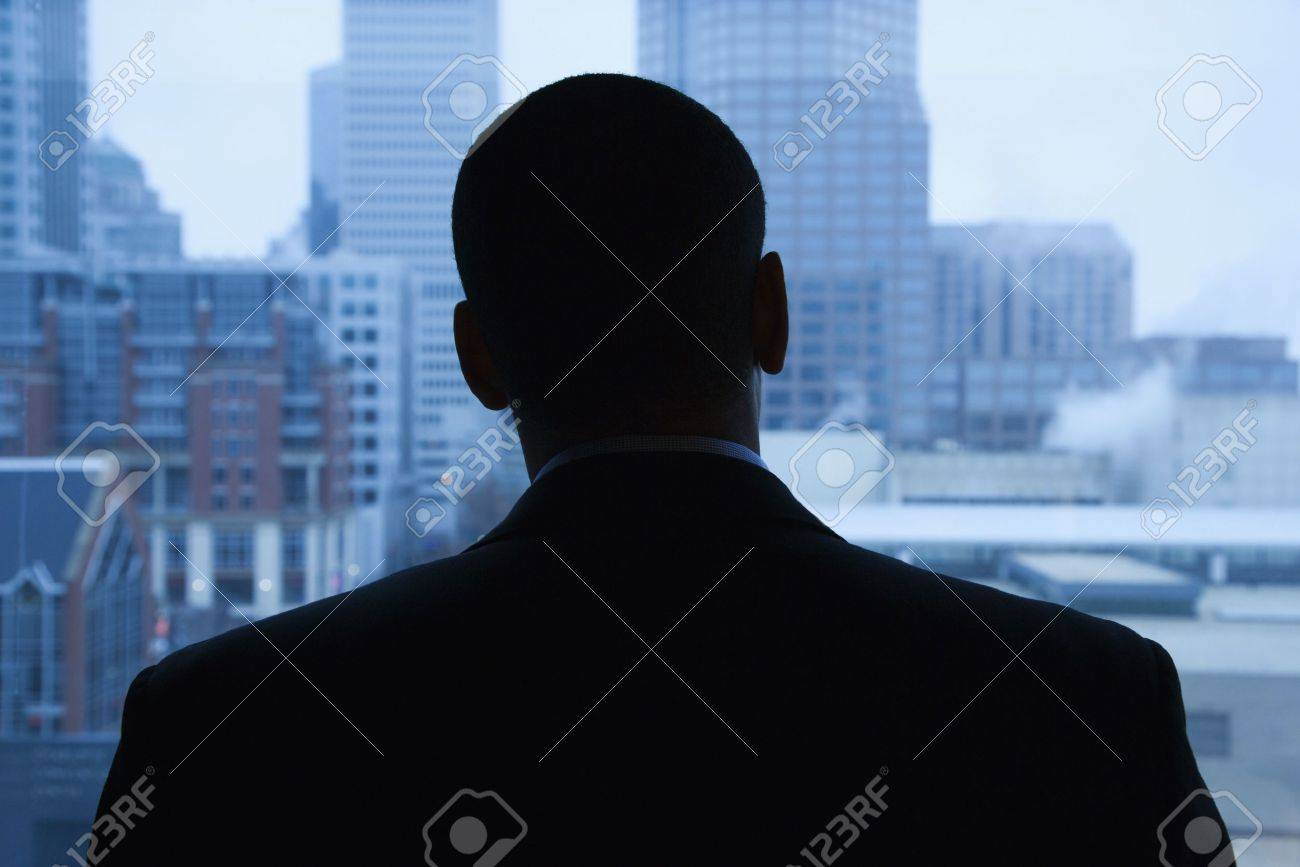 Rear view of an African-American businessman looking out of a window at the city in the distance. Horizontal shot. Stock Photo - 6395937