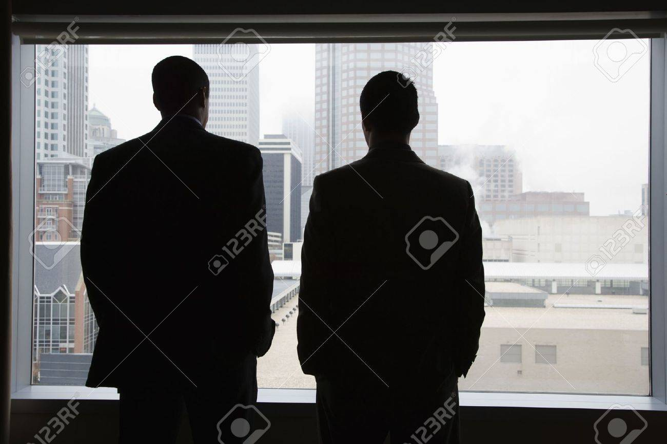 Rear view of two businessmen as they stare out a large window with a city view. They have their hands in their pockets. Horizontal view. Stock Photo - 6395706