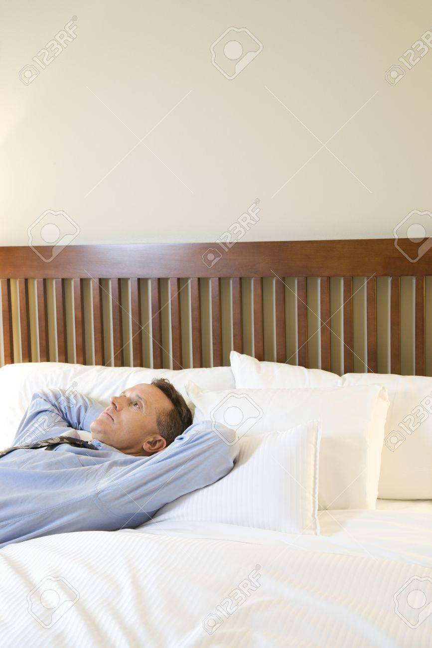 Caucasian businessman stares up towards the ceiling as he lies down with his hands behind his head. Vertical shot. Stock Photo - 6455276