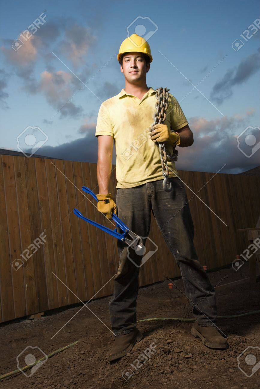 Attractive male construction worker in a hardhat stands at a construction site with bolt cutters and a chain. Vertical shot. Stock Photo - 6455300