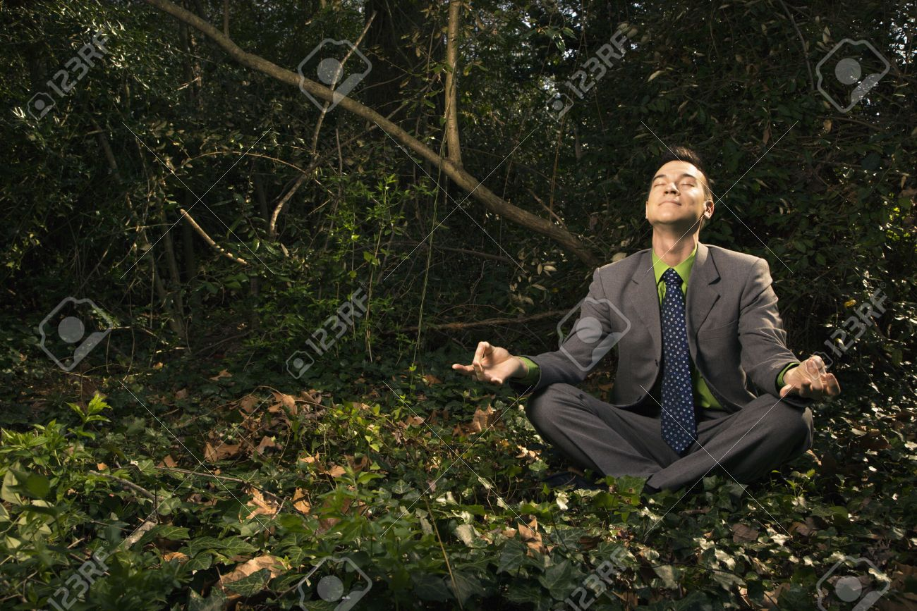 Young businessman sits in a lotus position meditating in the woods with closed eyes and a smile. Horizontal shot. Stock Photo - 6455434