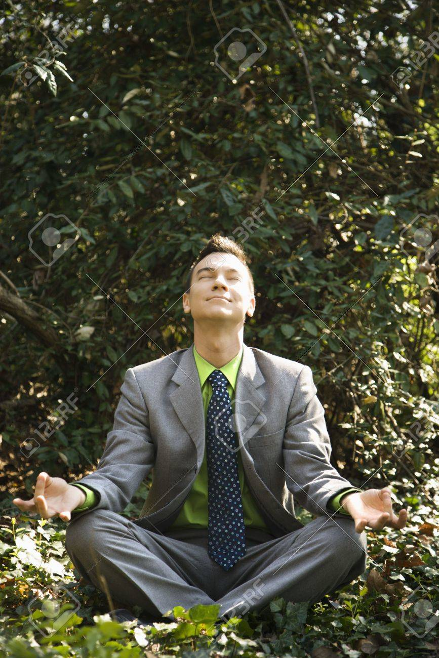 Young businessman sits in a lotus position meditating in the woods with closed eyes and a smile. Stock Photo - 6455452