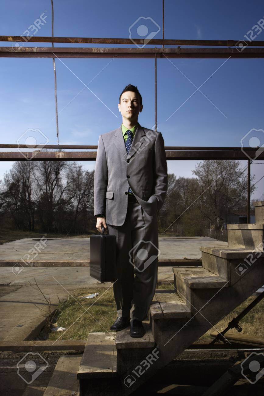 Young businessman holds a briefcase while standing on a wooden staircase in an abandoned building. Vertical shot. Stock Photo - 6455294