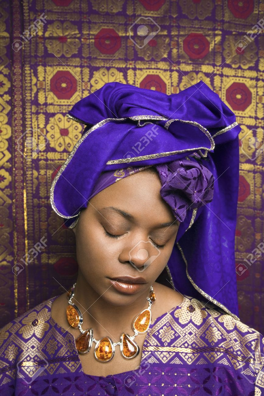Portrait of an African American woman wearing traditional African clothing and closing her eyes in front of a patterned wall. Vertical format. Stock Photo - 6497209