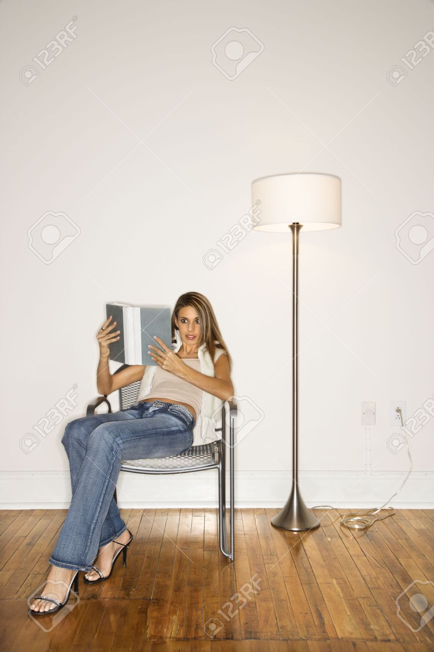 Attractive Young Woman Sitting Back In A Silver Chair And Reading Stock Photo Picture And Royalty Free Image Image 6420530