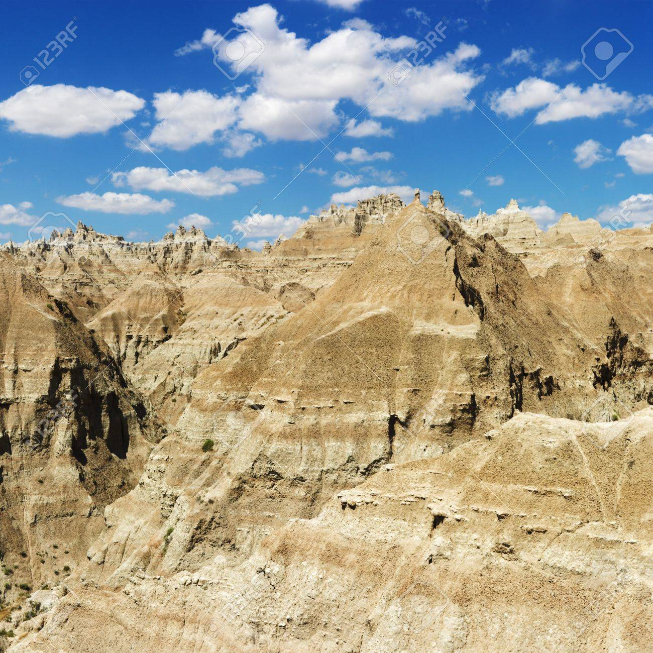 Mountain terrain in Badlands National Park, South Dakota, beneath blue sky and clouds. Square format. Stock Photo - 6913386