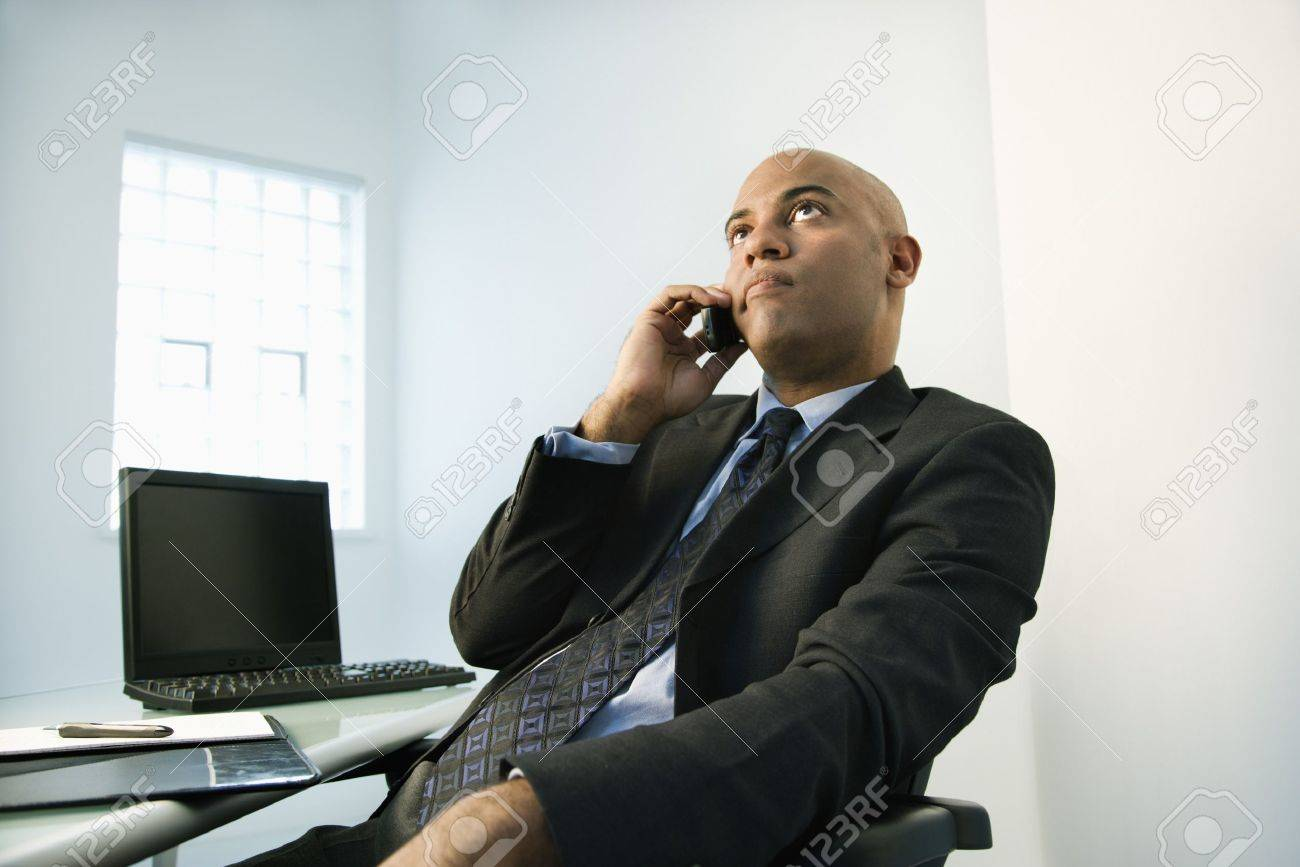 Frustrated office worker on the phone holding stock photo image - Frustrated Phone African American Businessman Holding Cellphone To Ear Looking Bored