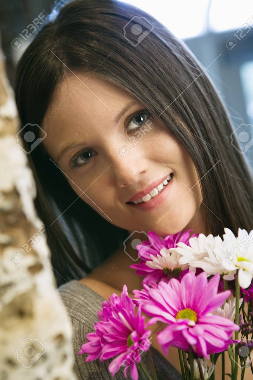 Portrait of pretty young Caucasian woman holding bouquet of flowers smiling. Stock Photo - 6924744