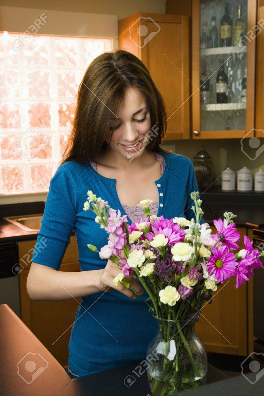 Pretty Caucasian young woman arranging flowers in vase in kitchen. Stock Photo - 6924790