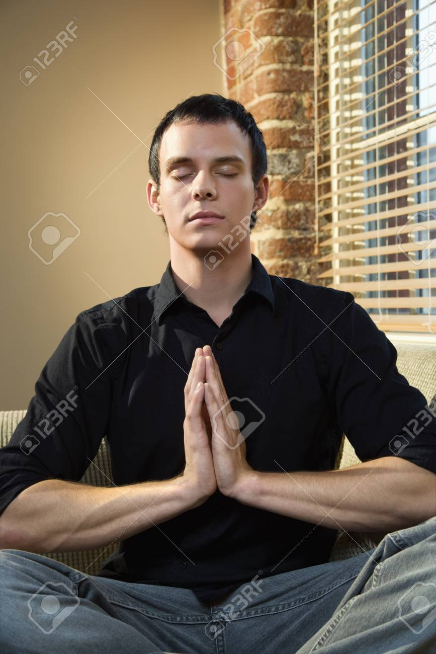 Young Caucasian man sitting on sofa meditating. Stock Photo - 6924768