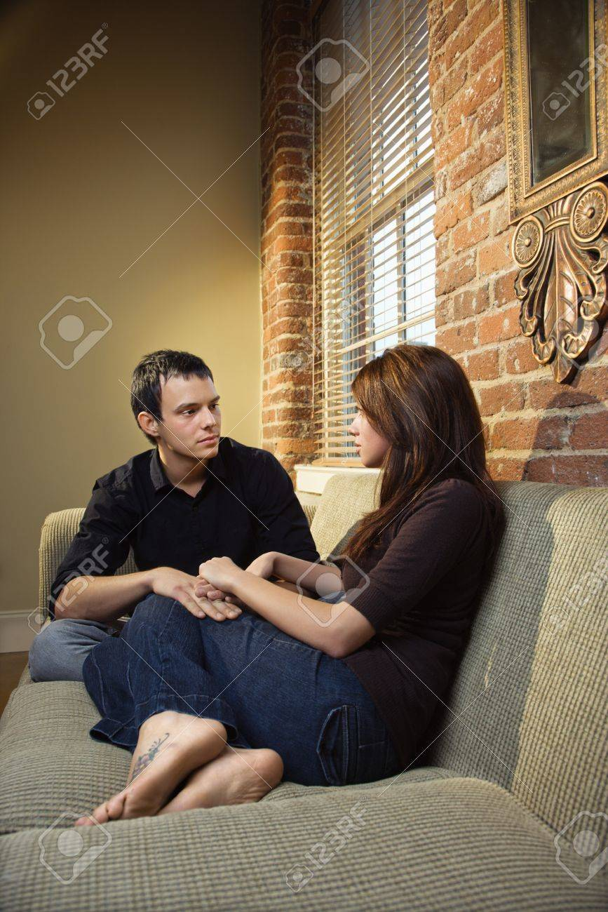 Young Caucasian couple sitting on living room sofa holding hands. Stock Photo - 6924813