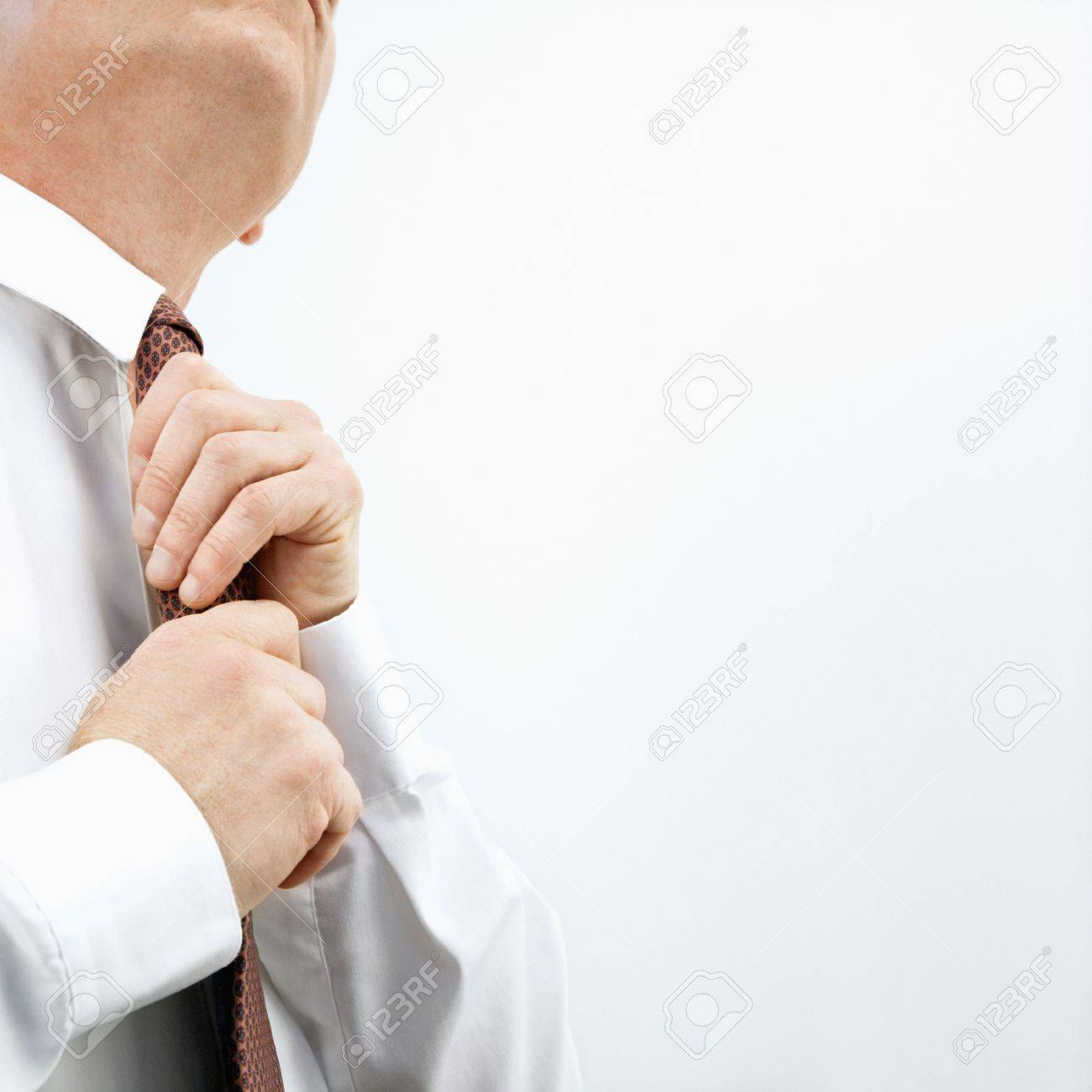 Caucasian middle aged businessman fixing necktie. Stock Photo - 6924758