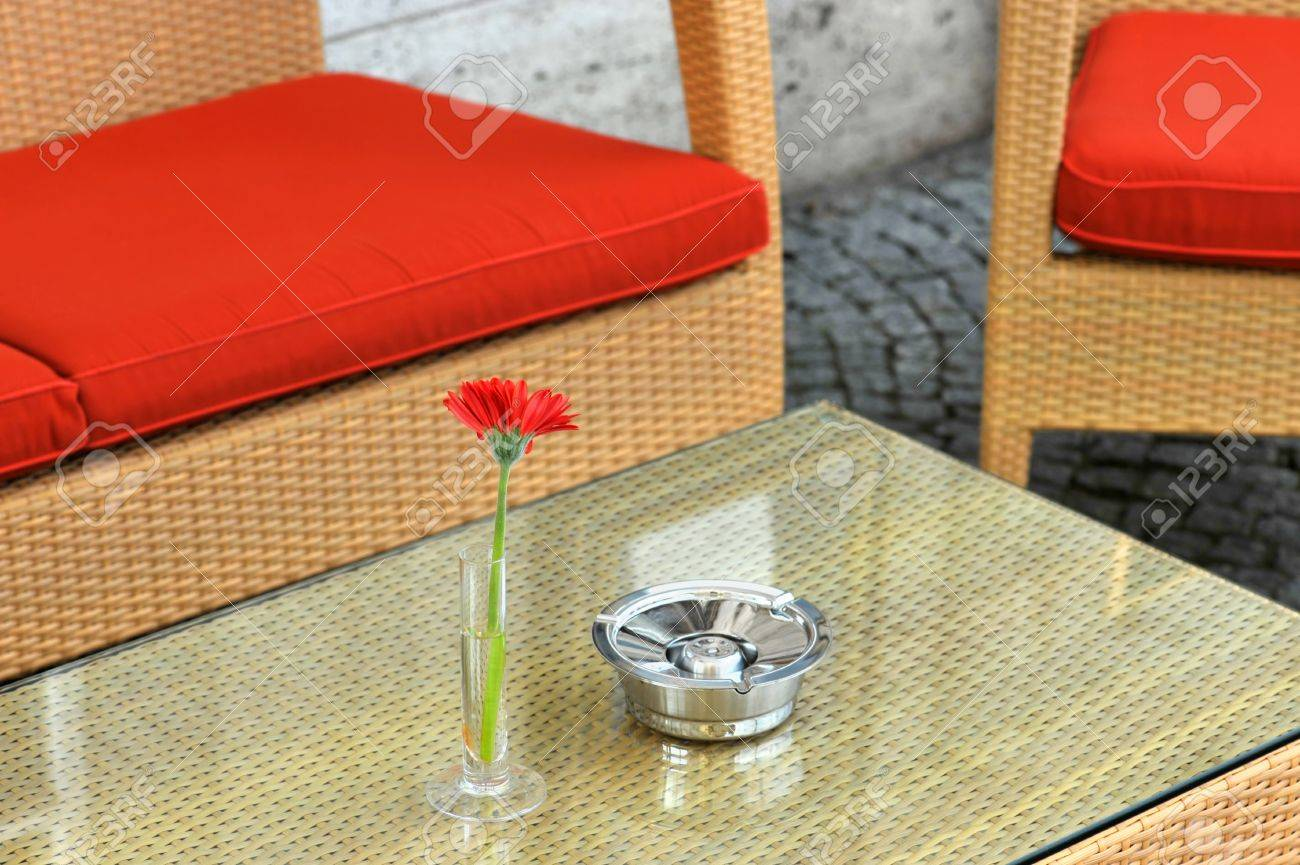 Hotel exterior with table, red chairs, red flower and ashtray Stock Photo - 6978235