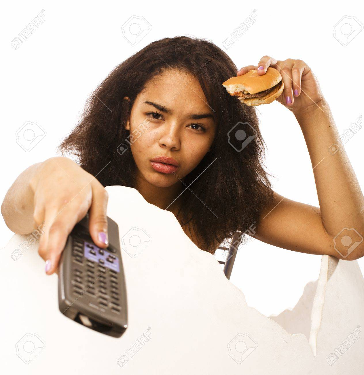 Stock Photo - young fat african american teen girl with remote and  hamburger isolated, unhealthy obsessed on white