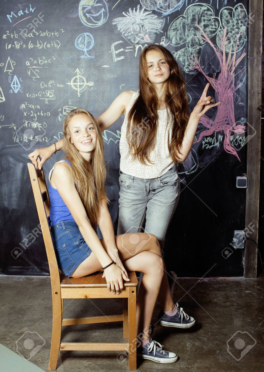 real school girls back to school after summer vacations, two teen real girls in classroom  with blackboard painted